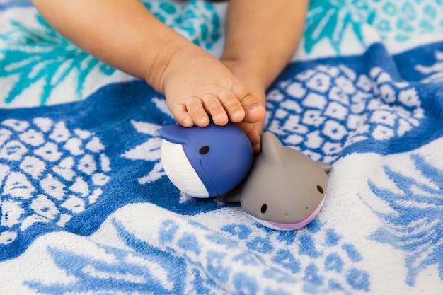 Piedi della neonata con i giocattoli di gomma sull'asciugamano di estate