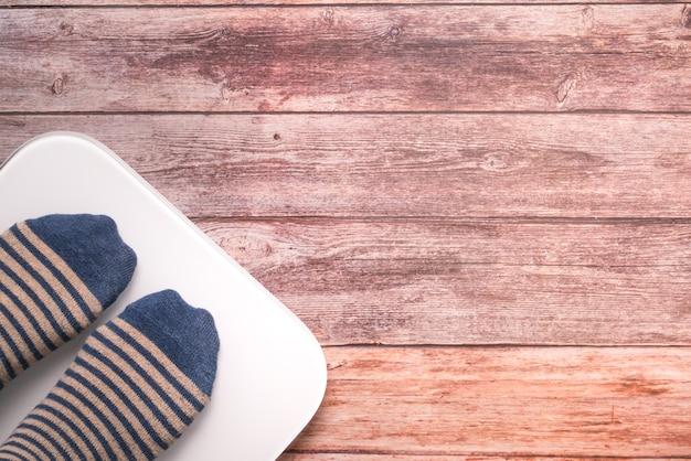 Piedi delle donne che stanno sulla bilancia digitale bianca sui precedenti di legno