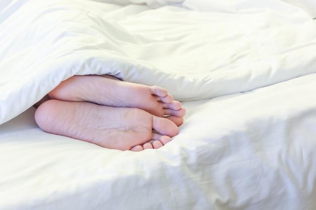 Piedi di donna addormentata in camera da letto bianca