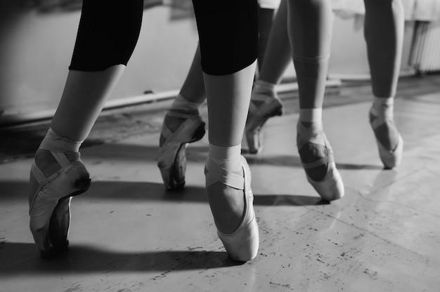 Piedi di giovani ballerine in scarpe da punta primo piano sullo sfondo di una classe di balletto