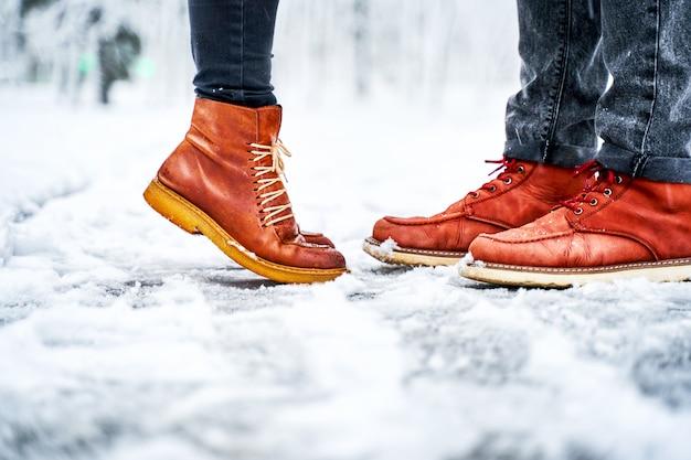 Piedi di una coppia su un marciapiede nevoso in stivali marroni