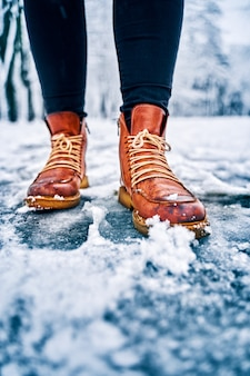 Piedi di una donna su un marciapiede nevoso con stivali marroni