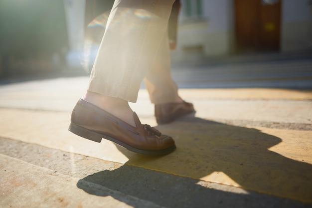 Piedi di uomini d'affari che camminano nella zebra crosswalk