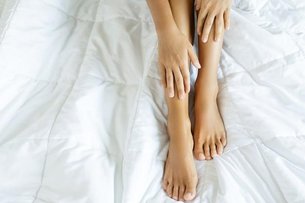 Piedi e mani femminili su biancheria da letto morbida