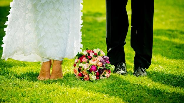 Piedi e scarpe sposi sull'erba nel giardino e bouquet da sposa