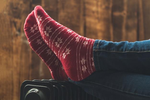 Piedi femminili a natale, caldi calzini invernali sul riscaldamento. resta caldo in inverno, serate fredde. stagione di riscaldamento