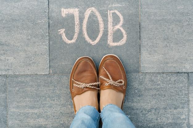 Piedi femminili con il lavoro di testo scritto sul marciapiede grigio