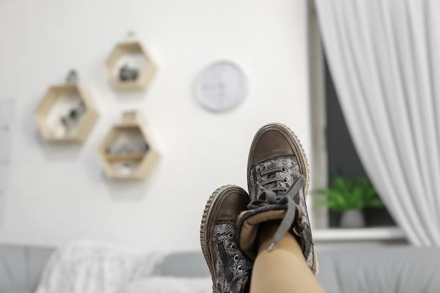 Piedi femminili con le scarpe grigie che si rilassano sulla tavola di legno