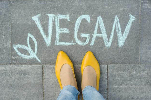 Piedi femminili con testo vegan scritto sul marciapiede grigio