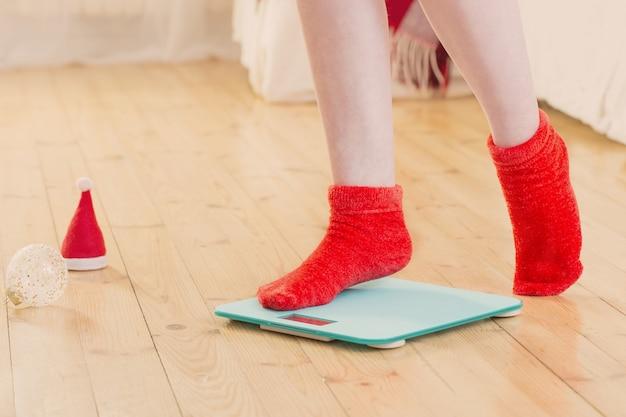 Piedi femminili in piedi su bilance elettroniche blu per il controllo del peso in calzini rossi con decorazioni natalizie
