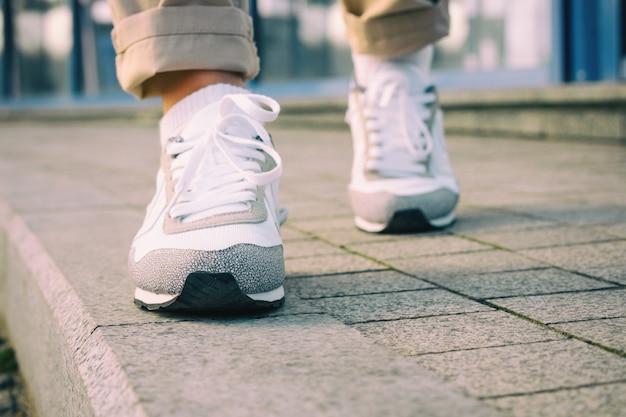 Piedi femminili in scarpe da tennis bianche che camminano sul marciapiede
