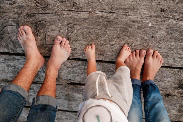 Piedi nudi della famiglia. ponte di legno. mamma, papà e bambino camminano a piedi nudi sul ponte di legno. giovane famiglia felice di trascorrere del tempo insieme. il concetto di vacanza in famiglia. copia spazio. messa a fuoco selettiva