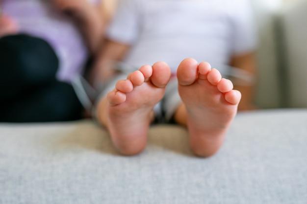 Piedi nudi per bambini. i piedi nudi del bambino sul pavimento di legno