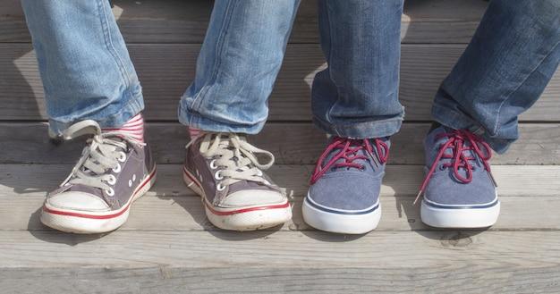 Piedi per ragazzi con scarpe da ginnastica. bambini seduti sulle scale in legno. giornata di sole all'aperto