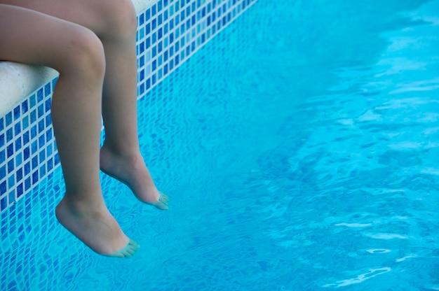 Piedi rinfrescanti in piscina in estate