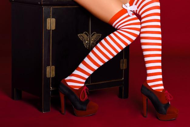 Piedini della donna con calze a righe rosse e bianche su sfondo rosso