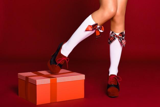Piedini della donna con calze di natale con un regalo