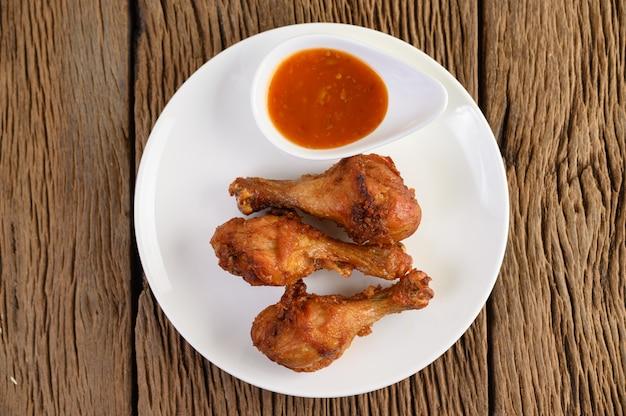Piedini di pollo fritto su una zolla bianca con salsa.