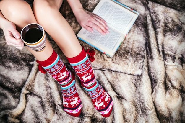 Piedini femminili in calze di natale con un libro e una tazza di caffè