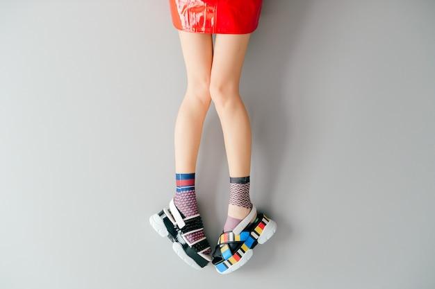 Piedini femminili in calzini alla moda non corrispondenti e scarpe sopra grigio