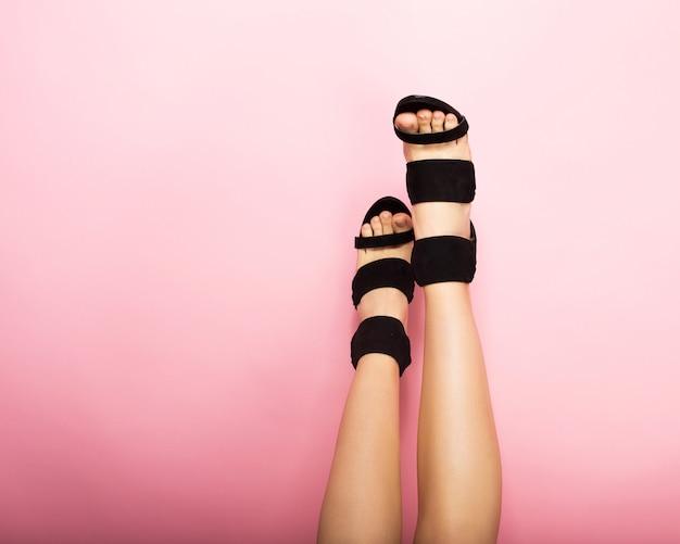 Piedini femminili su tacchi alti neri su sfondo rosa
