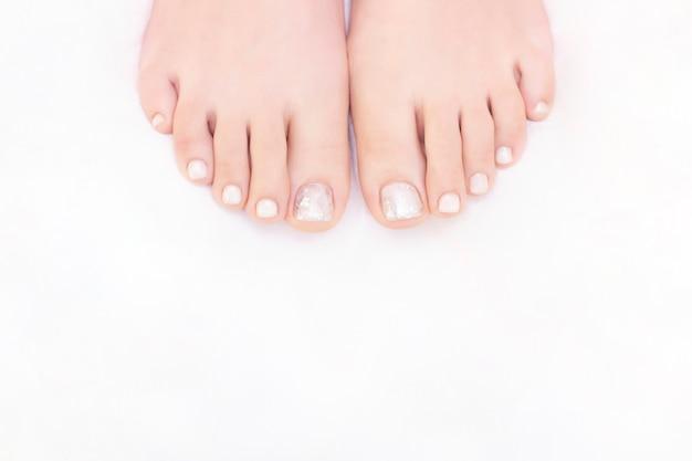 Piedini femminili su uno sfondo bianco. le unghie hanno un aspetto fresco e ordinato durante la procedura di pedicure. chiuda in su dei piedini femminili nel salone della stazione termale.