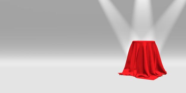 Piedistallo coperto con un panno rosso illuminato da faretti