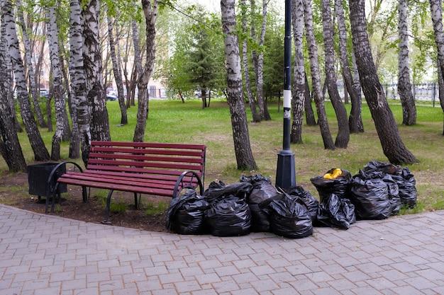Pieno di immondizia sacchetti di plastica nera in natura, in un parco pubblico, lungo la strada, accanto alla panchina. pulizia di primavera o autunno della città dal fogliame dell'anno scorso. protezione ambientale