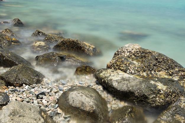 Pietra in mare e onda in mattinata con lunga esposizione