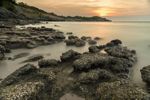Pietra in mare e onda sul tempo tramonto con lunga esposizione a ko sichang district chonburi