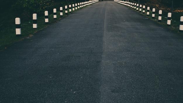 Pietra miliare accanto alla strada sulla parete della diga e sul paesaggio naturale fondo di idea di concetto di viaggio stradale di viaggio del segnale stradale di nakhonnayok tailandia