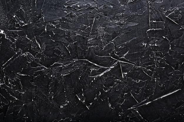 Pietra nera trama muro con graffi bianchi. schermo intero come