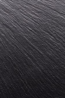Pietra nera, trama per lo sfondo. ombre lisce e luce sulla superficie strutturale