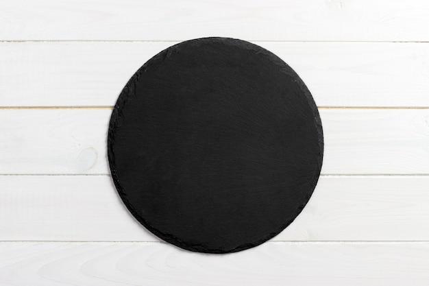 Pietra rotonda dell'ardesia nera su fondo di legno, vista superiore, spazio della copia