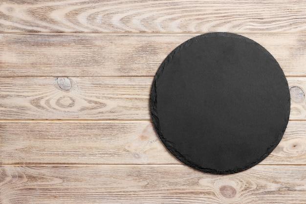 Pietra rotonda dell'ardesia nera su superficie di legno, vista superiore, spazio della copia