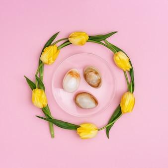 Pietra uova di pasqua e bouquet di bellissimi tulipani gialli. composizione in stile minimal con il concetto di pasqua. fiori di primavera. vista dall'alto e copia spazio.