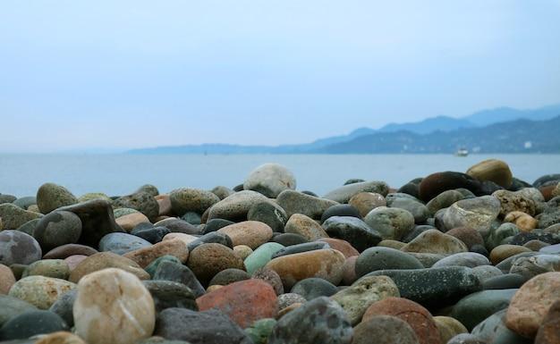 Pietre di ghiaia sulla spiaggia con vista sul mare sfocata