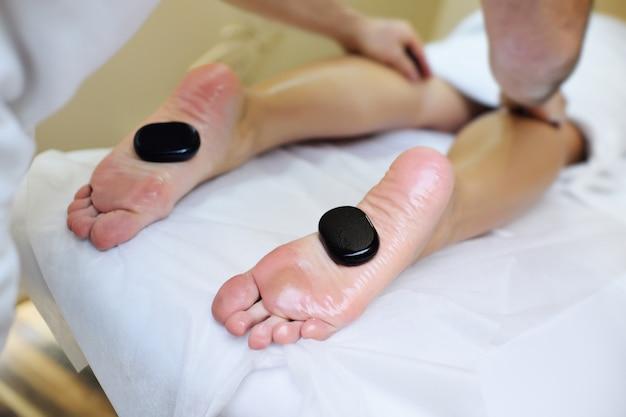 Pietre per la terapia della pietra ai piedi di una giovane donna. relax, spa, massaggi