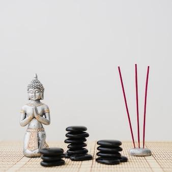 Pietre vulcaniche, bastoncini di incenso e figura di buddha