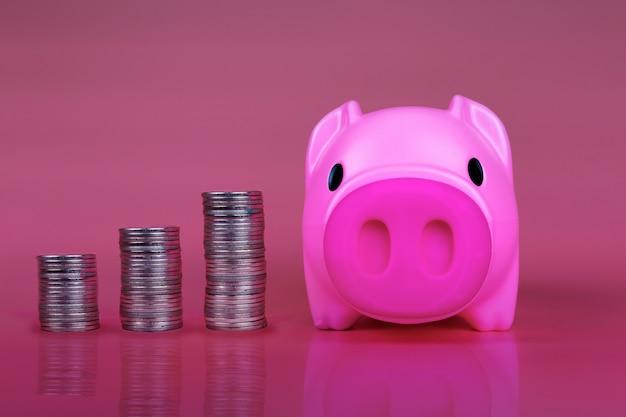 Piggy banca rosa con monete di crescita che significa concetto di successo del business grwoth.