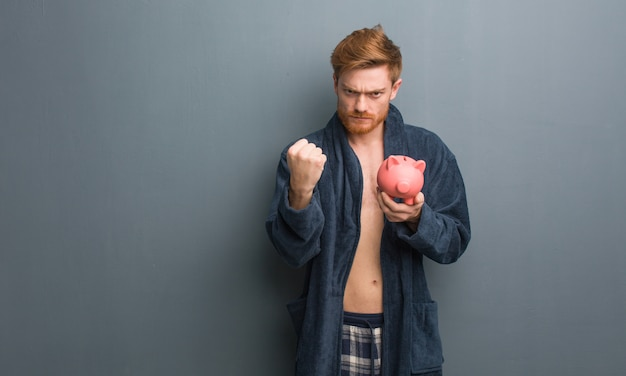 Pigiama d'uso del giovane uomo di redhead che mostra pugno alla fronte, espressione arrabbiata. ha in mano un salvadanaio.