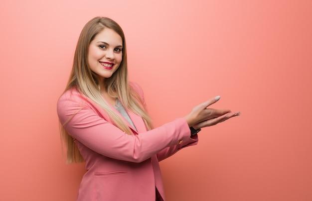 Pigiama d'uso della giovane donna russa che tiene qualcosa con le mani