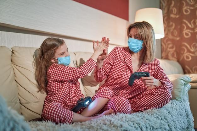 Pigiama d'uso della ragazza e della donna e maschere protettive mediche che si siedono sul sofà in salone con la quarantena automatica di isolamento dei controllori del videogioco a casa, covid-19.