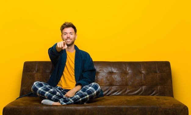 Pigiama da portare del giovane che indica alla macchina fotografica con un sorriso soddisfatto, sicuro, amichevole, scegliente. seduto su un divano