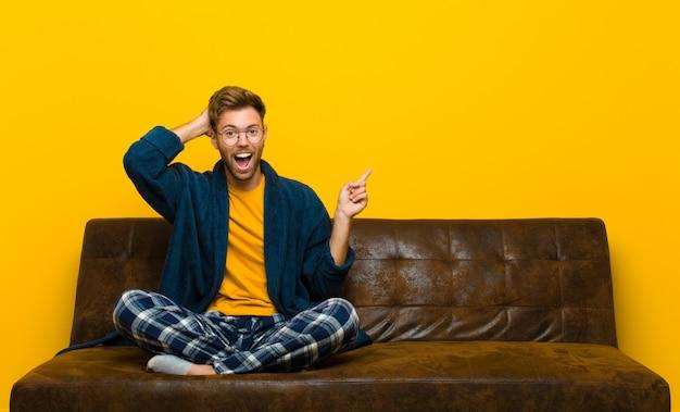 Pigiama da portare del giovane che ride, che sembra felice, positivo e sorpreso, realizzando una grande idea che indica il copyspace laterale. seduto su un divano