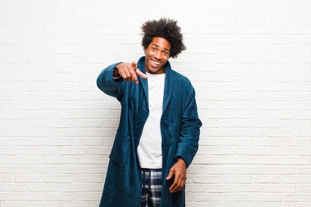 Pigiama da portare del giovane uomo di colore con l'abito che indica alla macchina fotografica con un sorriso soddisfatto, sicuro, amichevole, scegliente contro il muro di mattoni