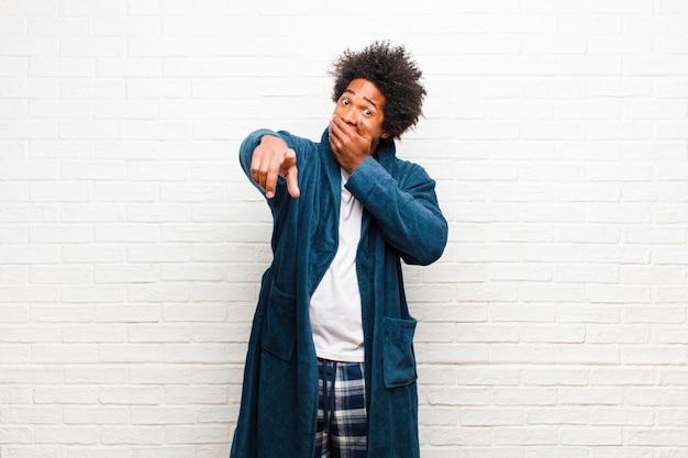 Pigiama da portare del giovane uomo di colore con l'abito che ride di voi che indica la macchina fotografica e che vi prende in giro o che vi prende in giro contro il muro di mattoni