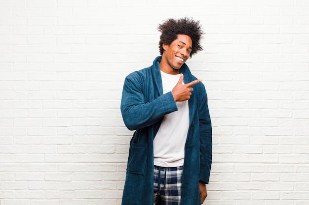 Pigiama da portare del giovane uomo di colore con l'abito che sembra eccitato e sorpreso indicando il lato e verso l'alto per copiare spazio contro il muro di mattoni