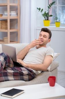 Pigro marito sdraiato sul divano e sbadigliando.