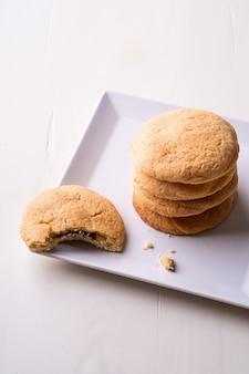 Pila casalinga di biscotti al cioccolato di pasta frolla con un biscotto pungente sulla tavola di legno del piatto bianco
